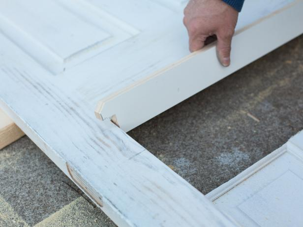 Use a hand saw to cut the strip, then place it along the bottom of the door opening. Secure the ledge into place using wood glue, nails and a hammer. For a more decorative look, add pressure-treated crown molding under ledge.