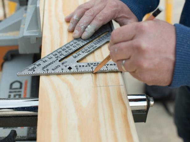 On the 2' x 6' plank of pine or cedar, mark the width of the door span,  adding one additional inch to each side to account for proper overhang.