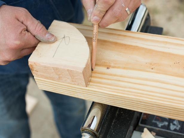 Create a quarter circle template by tracing a round edge onto two pieces of scrap pine or cedar boards, then cut the pattern onto the 2' x 6' plank.