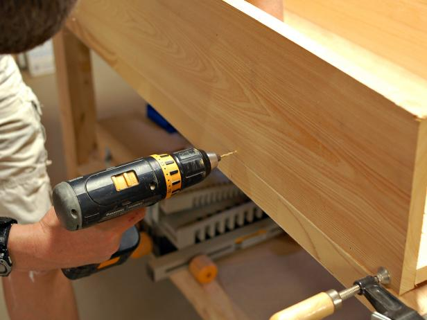 Use drill to attach parts of window box together with screws along length of box.