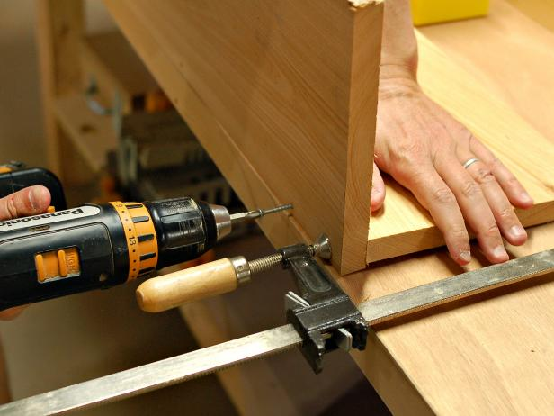 After gluing one part of window box to the other, hold with a clamp, and then use drill to screw pieces together for added strength and durability.