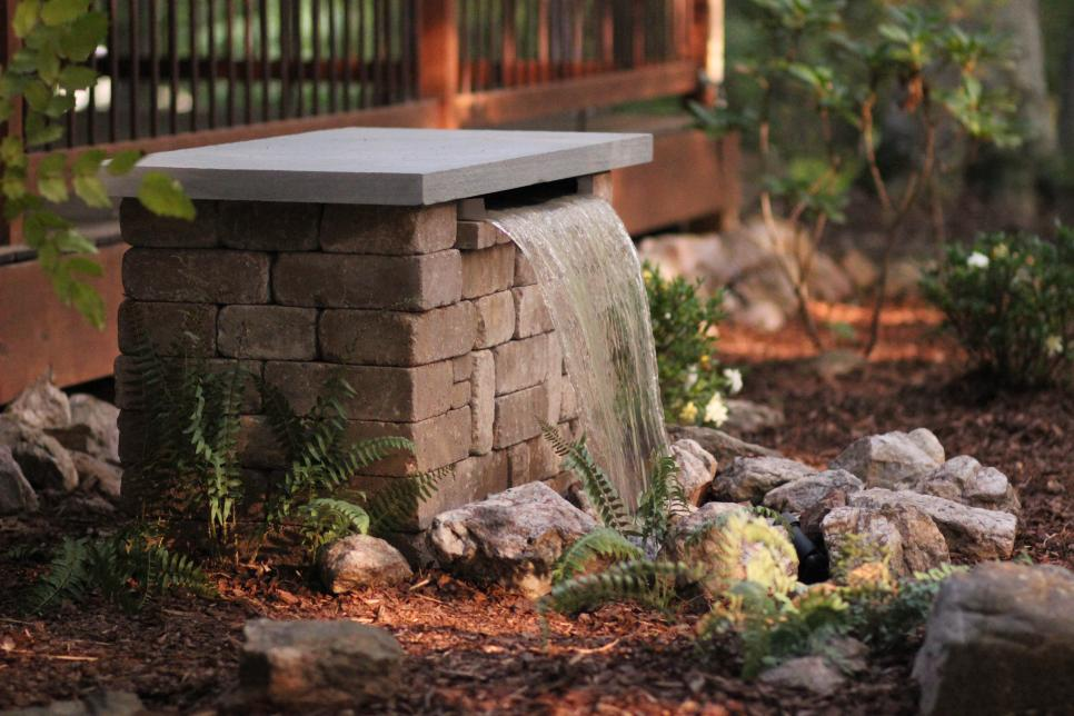 Build a stone waterfall fountain hgtv for Garden fountains and water features