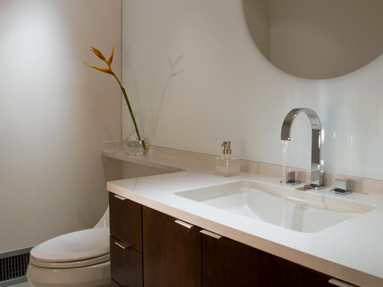 Bathroom Countertop Surface Options : bathroom with round mirror sleek chrome accents make this bathroom ...