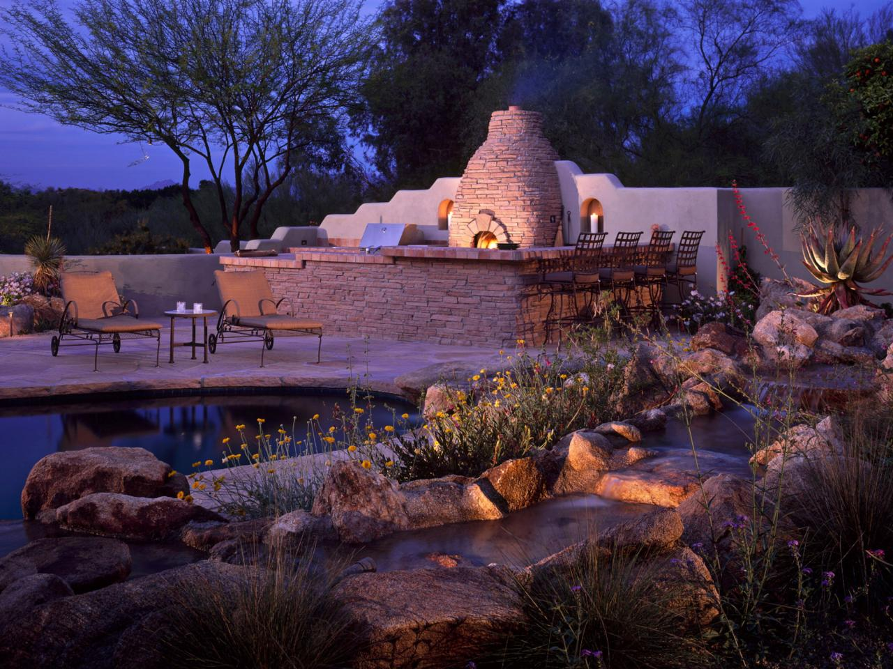 Outdoor Entertaining Area With Grill And Stone Fireplace, Bar Area With  Chairs, Pond With Plants, Rocks, And Flowers, Nighttime View Of Outdoor  Room.