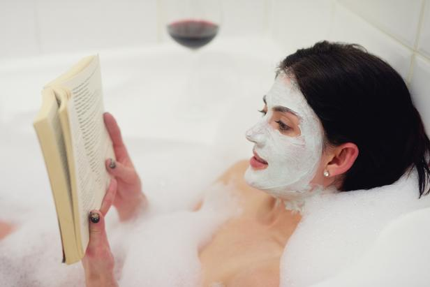 Woman Reading in Bath with Face Mask