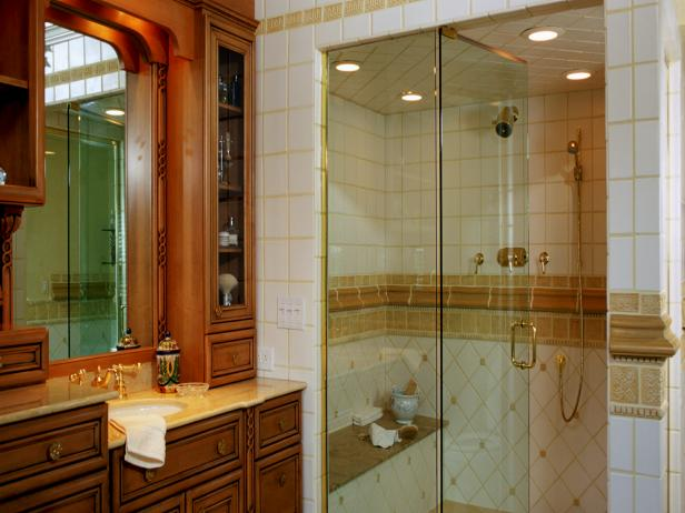 Glass Door Walk In Shower With White and Gold Interior Tile and Built in Bench Seat Beside Wood Vanity With Glass Door Cabinets