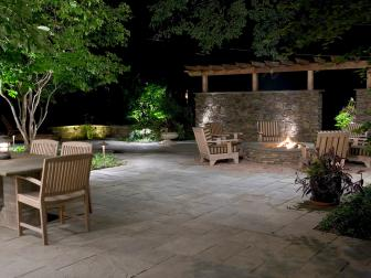Stone Patio With Round Fire Pit And Striped Outdoor Chairs