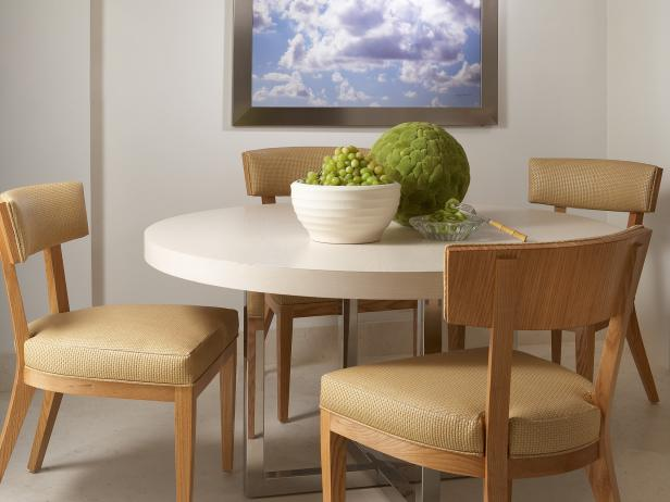 White Dining Room With Round White Table and Wood Chairs