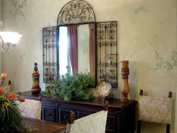 Room With Crackled Finished Walls and Ornate Iron Mirror Above Credenza
