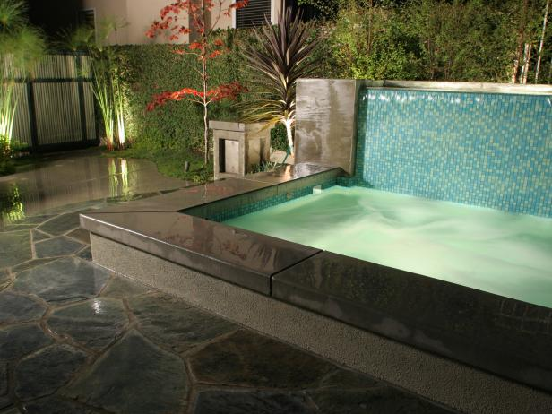 Contemporary Outdoor Spa With Blue Tile Wall and Cement Surround