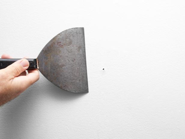 Comb wall surface with spackle knife to loosen up paint build-up or bumps. Fill nail holes with spackle and spackle knife. Once spackle has dried, sand with sanding block. Wipe entire wall with sponge dipped in warm water.