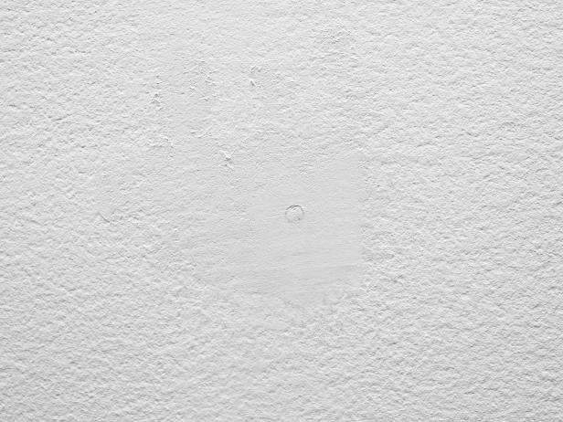 Spackle any holes in the wall surface and smooth with sandpaper before applying the wallpaper.