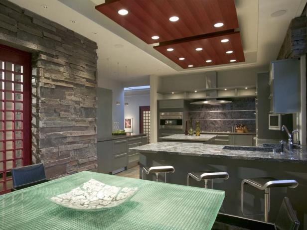 Modern Gray Kitchen With Stone Wall and Green Glass Dining Table