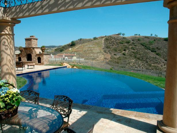 Contoured Infinity Pool With Outdoor Fireplace and Hillside View