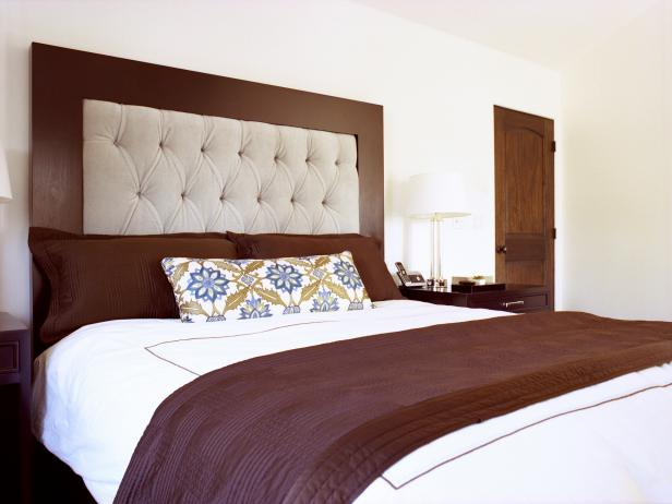 White Bedroom With Tufted Headboard and Brown Pillows