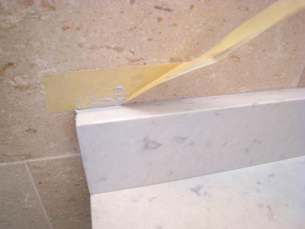 Carefully remove tape used to protect wall above where backsplash was installed. Using tape keeps caulk, paint and other project materials from staining the wall.
