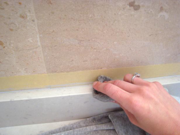 Use a straight blade to remove any large pieces of excess caulk. A rag with acetone will help further smooth the seams and clean up any residue from the caulk.