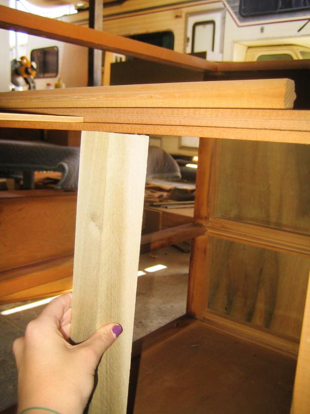 Using a saw, remove the original vertical support beam in the center back of the cabinet.
