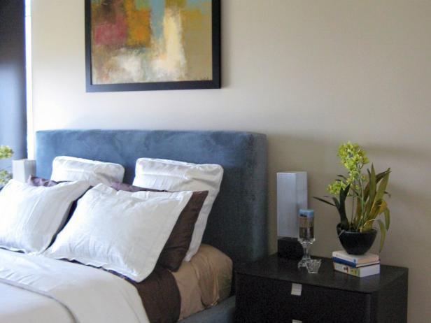 Brown Bedroom With Blue Upholstered Headboard and Multicolored Artwork