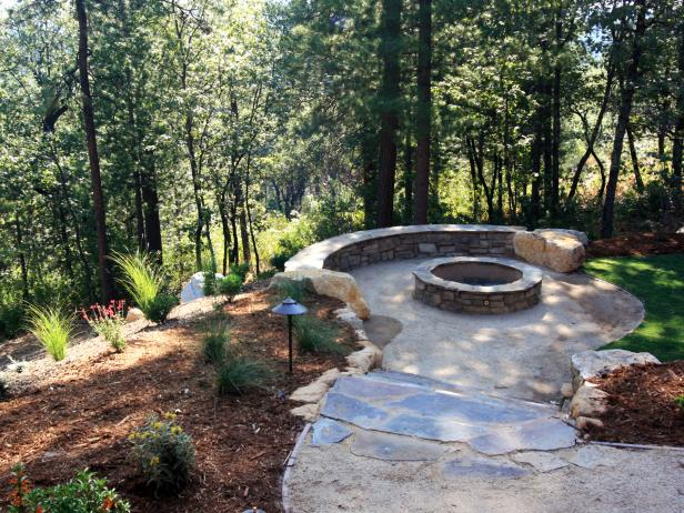 Outdoor Stone Fire Pit Surrounded By Bench and Landscaping