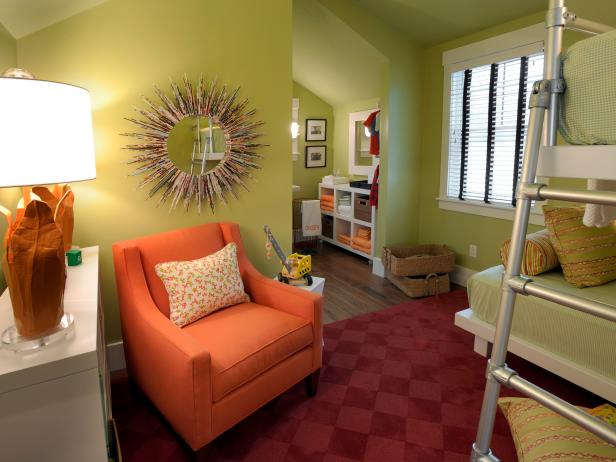 Green Bedroom With Orange Armchair, Sunburst Mirror and Red Area Rug