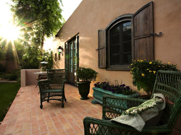 Southwestern Brick Patio With Green Wicker Chairs