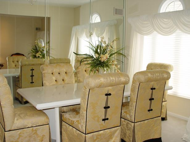 Gold Dining Room With Mirrored Wall, Upholstered Chairs & Marble Table