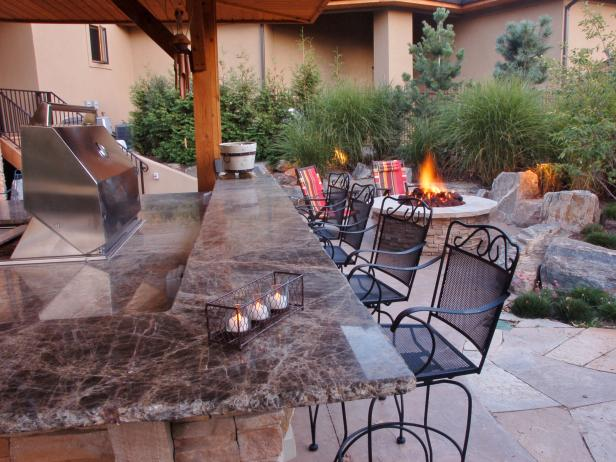Natural Feel Outdoor Kitchen With Granite Counters and Stone Fire Pit