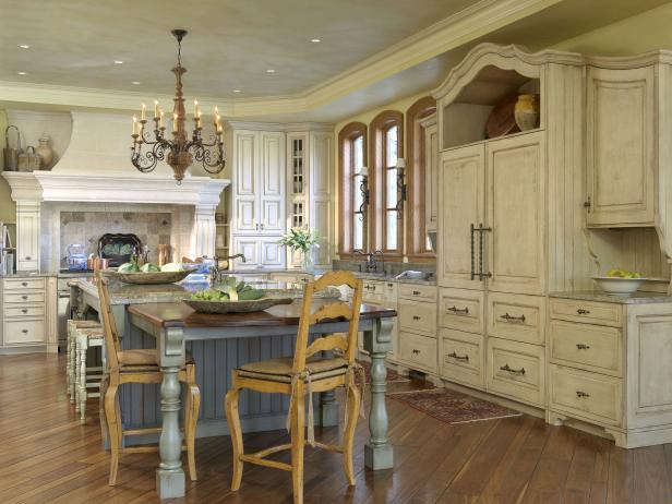 Old World Kitchen With Weathered Cabinets and Furniture-Style Island