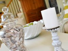 Coastal Style Table Decor With Seashell Filled Vase and Pillar Candle