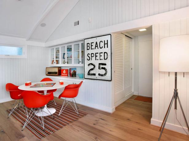 white coastal game room with beadboard walls and orange chairs