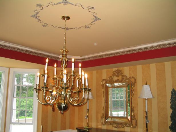 A gold chandelier hangs in a dining room with gold striped wallpaper.