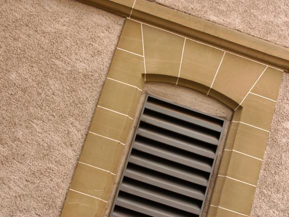 Stone Framed Wall Vent on Stucco Exterior