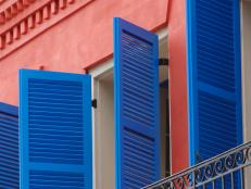 Striking Blue Shutters and Red Wall