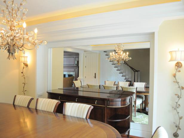 Neutral Dining Room With Large Mirror, Chandelier and Sconce Lighting