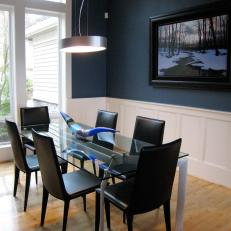 Contemporary Dining Room With Navy Accent Wall And Glass Table