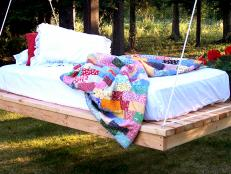 Hanging Outdoor Daybed With Multicolored Quilt