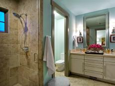 A private guest bathroom offers up a cool, calming palette and luxurious amenities.