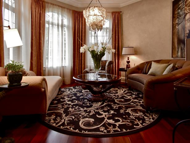 Brown Living Room With Chandelier and Round Area Rug