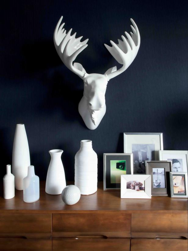 White Faux Moose Head on Dark Wall Above White Vases, Frames