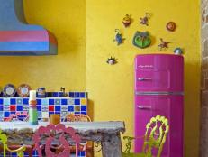 Yellow Spanish-Style Kitchen With Retro Pink Refrigerator