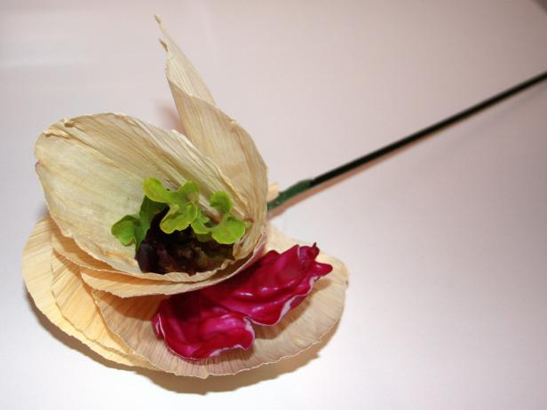 For a splash of color, secure baby greens between each petal with hot glue. Assemble 15 corn husk flowers.