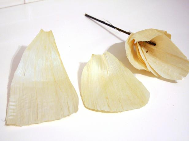 Using scissors, round edges of four to six cornhusks to resemble flower petals. Working in an overlapping, concentric pattern, hot glue cornhusk petals to skewer/plant stake.