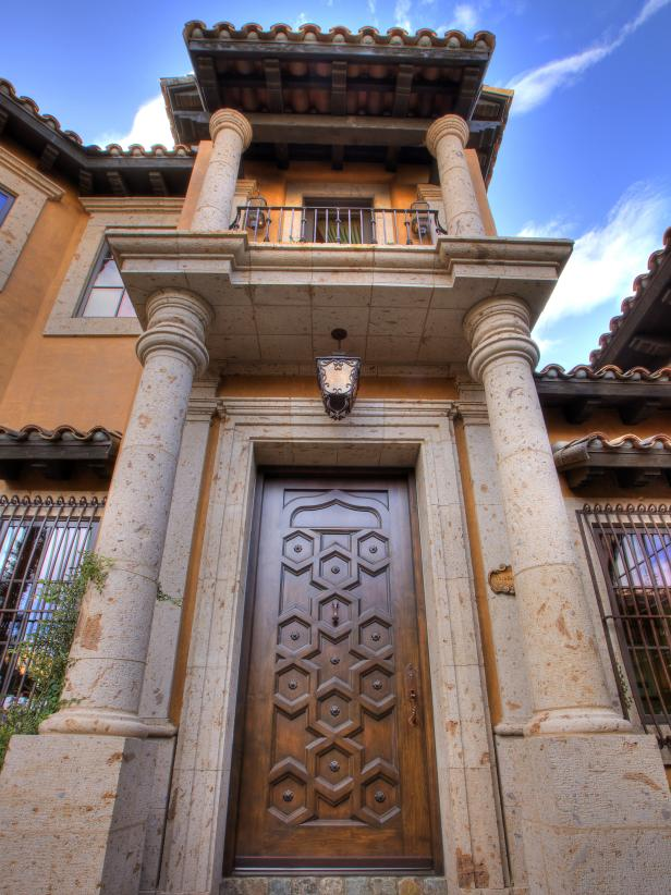 Exterior of Mediterranean Home With Columns, Balcony and Wood Door
