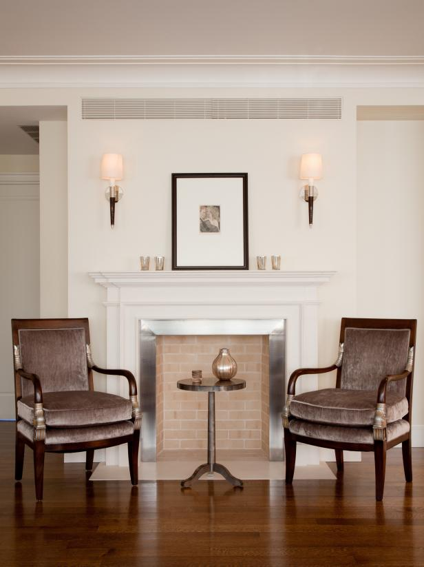 Brick Fireplace Flanked by Velvet Chairs & Sconces
