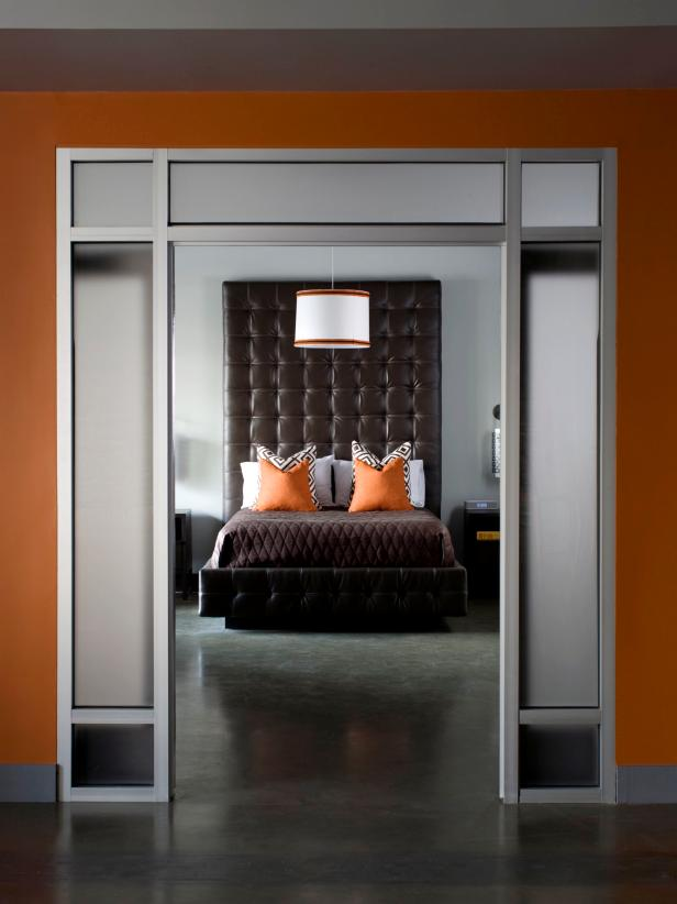 Brown Padded Headboard in a Modern Bedroom with Orange Accents