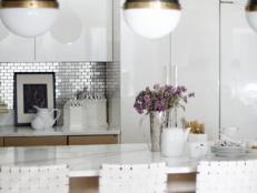 White Kitchen with Globe Pendant Lights and Metallic Accents