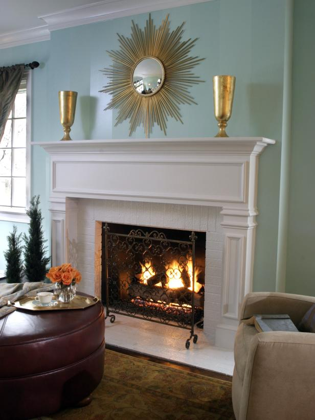 White Brick Fireplace in a Aqua Living Area With Gold Starburst Mirror
