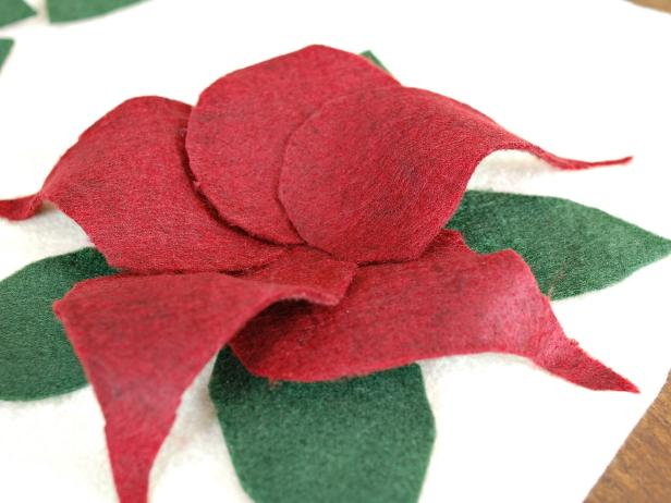 Stick the base of the petal in the center of the poinsettia, gently fold up and stick tip of petal to pillow, allowing it to arch slightly.