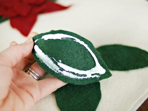 Apply fabric glue to the back of each leaf and stick it to the cream felt in the desired position.